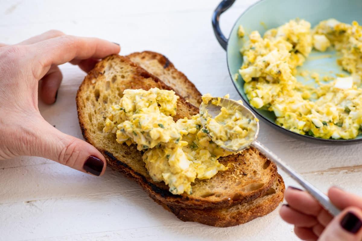 spooning egg salad onto toast