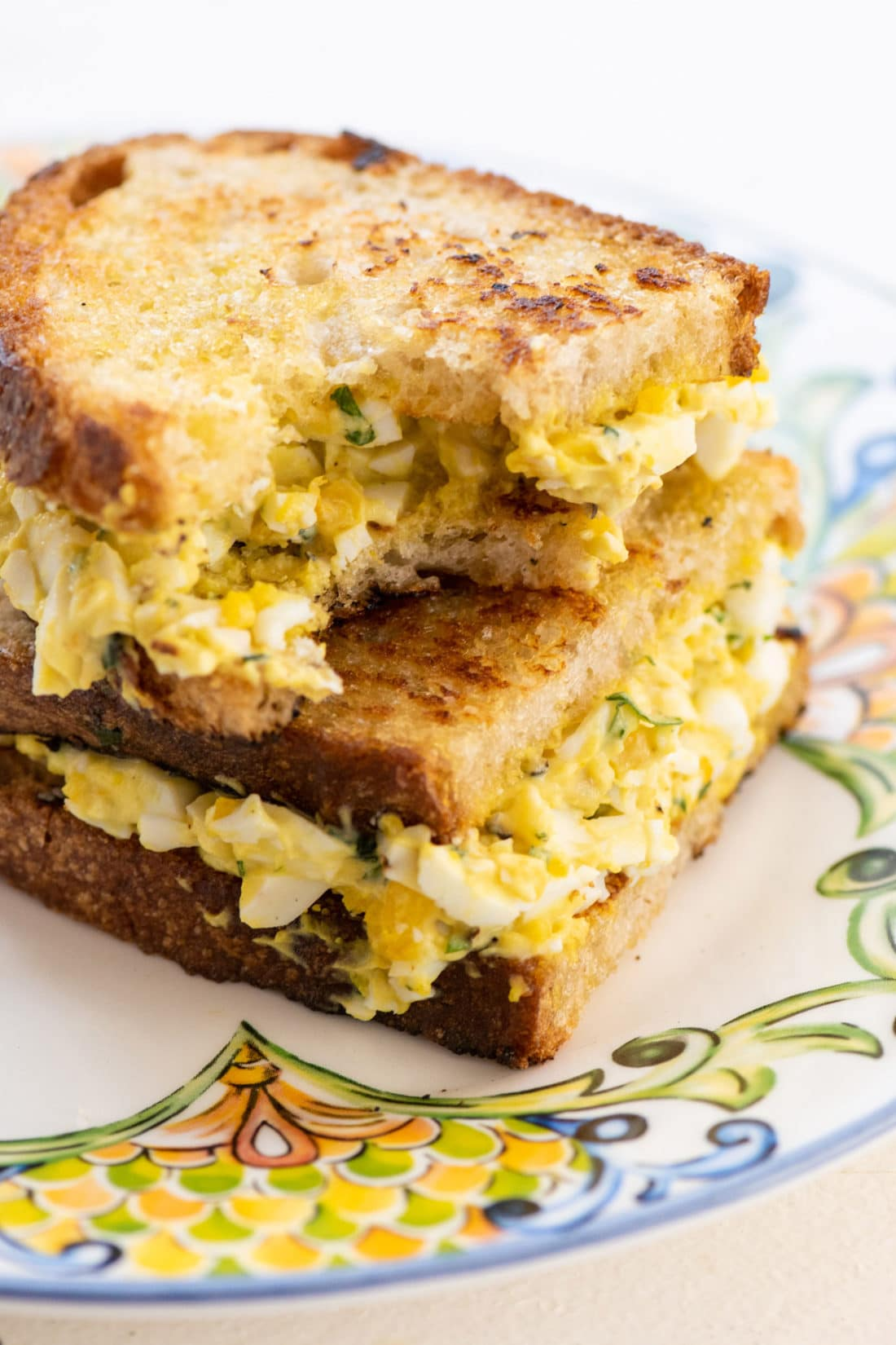 an egg salad sandwich with a bite taken out of it