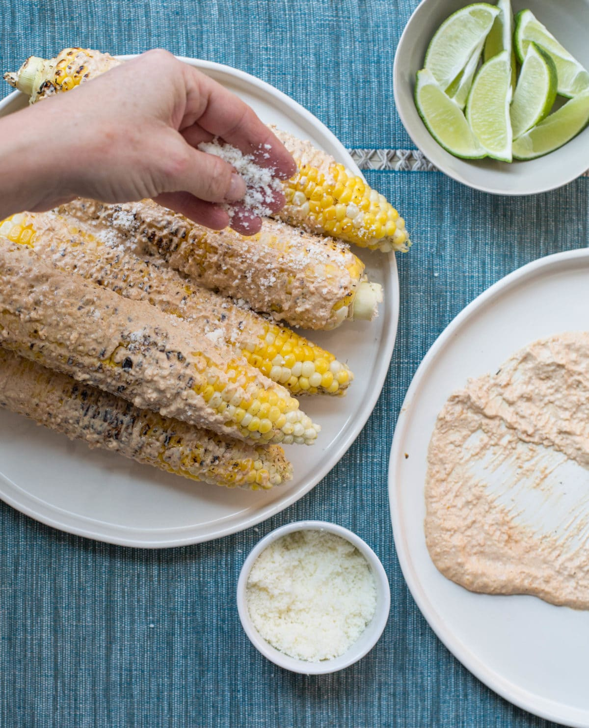 sprinkling Mexican Grilled Corn with cheese