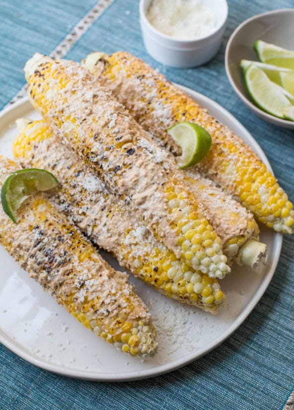 Elotes on a plate with limes