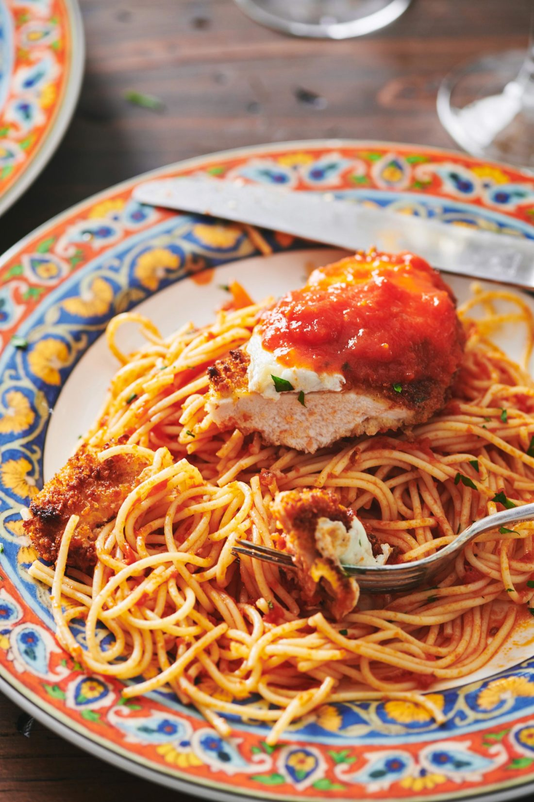 Chicken Parmigiana on a plate with spaghetti