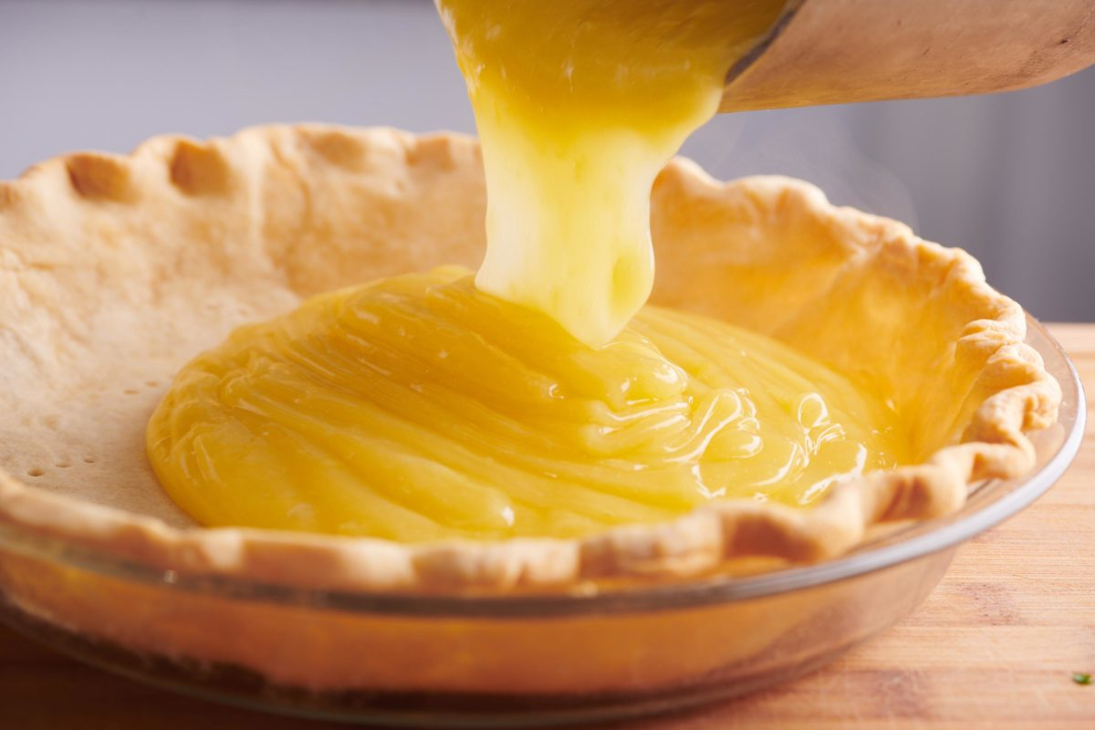 pouring lemon curd into a pie shell