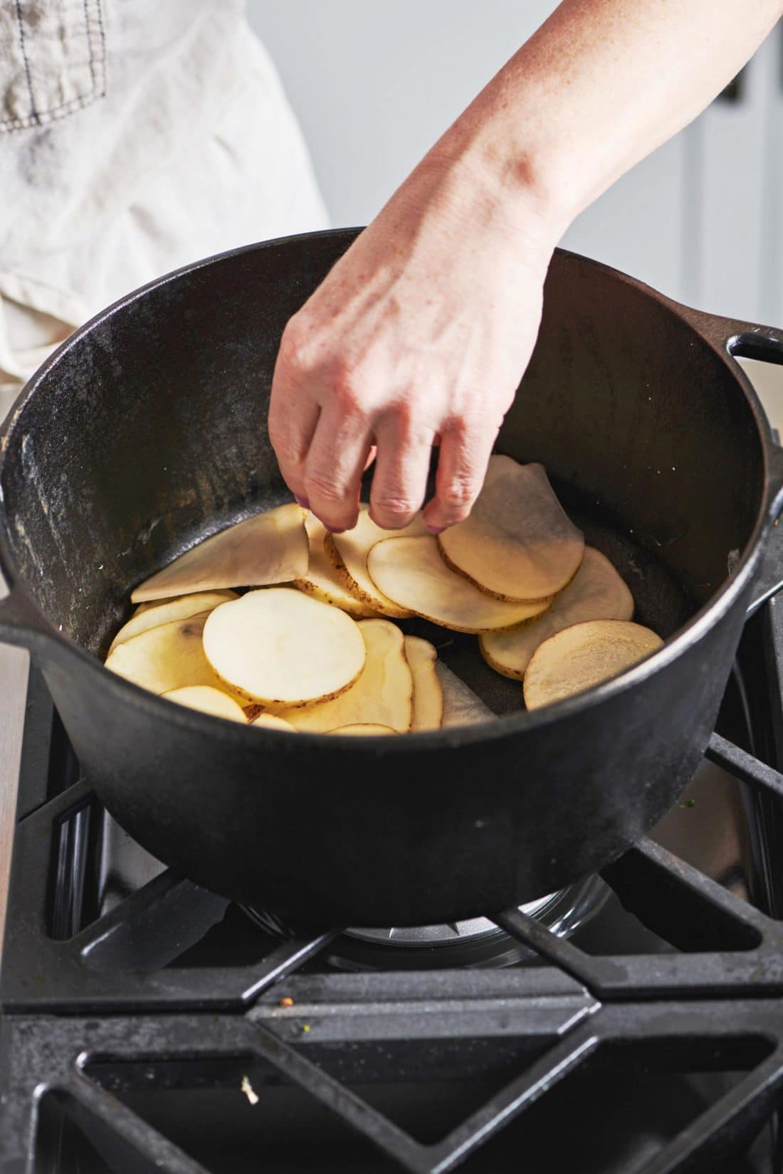 layering potatoes in a cast iron pot